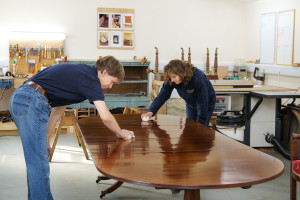 Martin and Andrea work on restoring a fine wooden table
